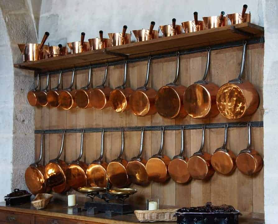 """copper pots hanging the wall with the title """"Kitchen Design Ideas for the 21st Century Homesteader - Stone Family Farmstead"""""""