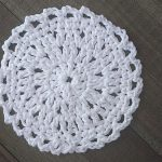 white crocheted coaster on a wood background